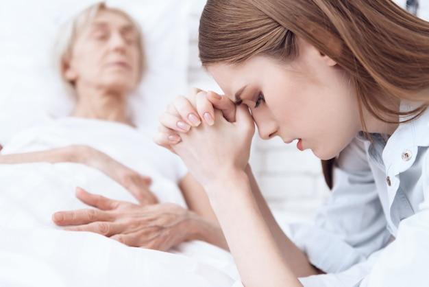 女性は気分が悪く、女の子が祈っています