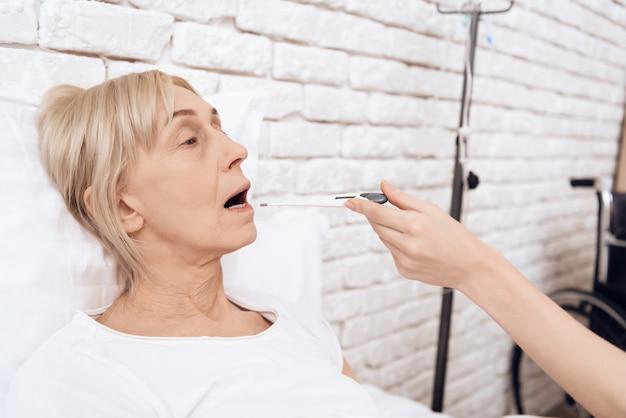 看護師は患者の体温計を口に当てます