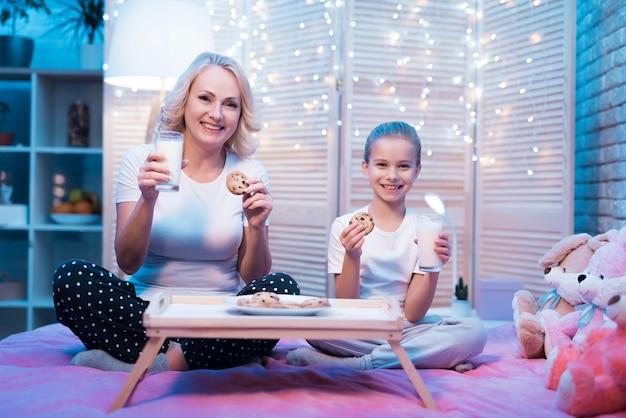 女の子と祖母は自宅でミルクとクッキーを食べています。