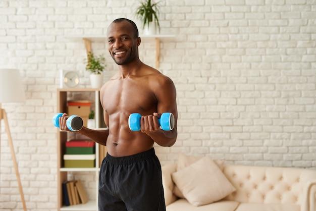 アフリカ系アメリカ人の運動選手がダンベルで筋肉をポンピング。