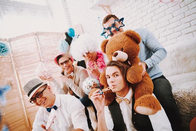 Гей парни в галстуках-бабочках вместе позирует на диване на вечеринке.