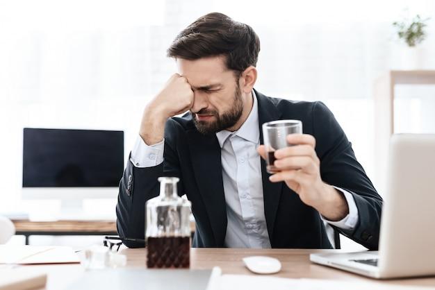 Мужчина пьет алкогольный напиток на рабочем месте.