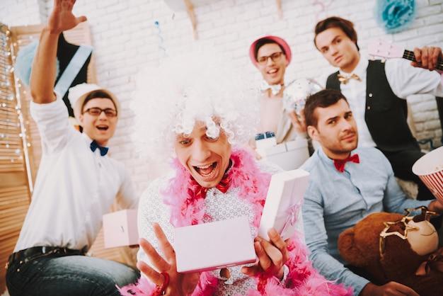 Гей парни в галстуках открывают подарки на вечеринке.