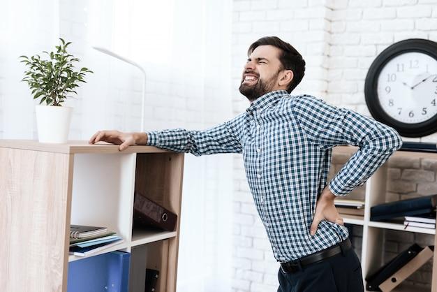 У мужчины болит спина. он держит руки на талии.