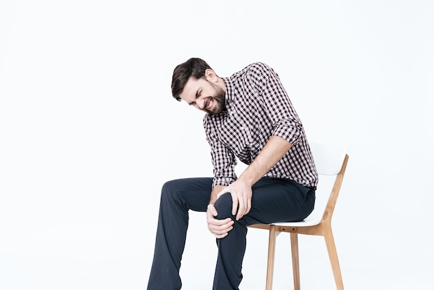 У молодого человека болит нога. он массажирует одну ногу.