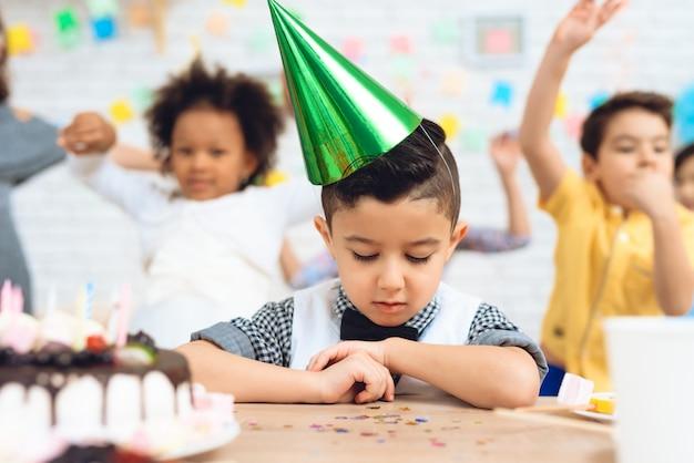 緑のお祝い帽子の少年はケーキとテーブルに座っています。