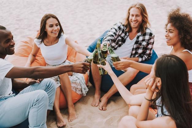 Молодые люди чокаются от пивных бутылок на пляже