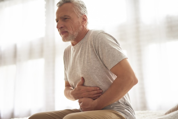腹部の胃の痛みを保持している老人が患者を傷つけます。
