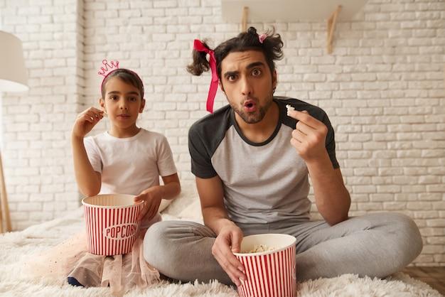アラブ人と女の子はベッドでポップコーンを食べています。