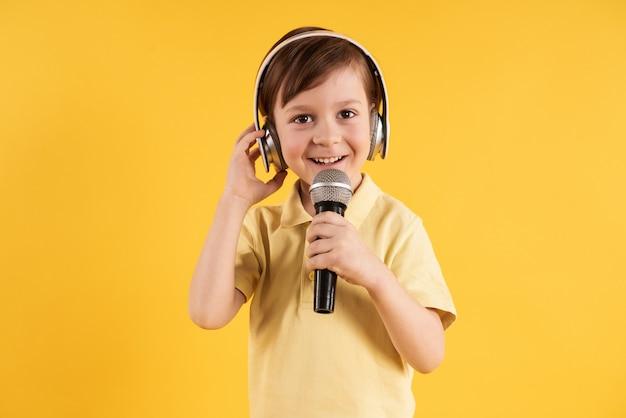 Маленький мальчик в наушниках поет в караоке.
