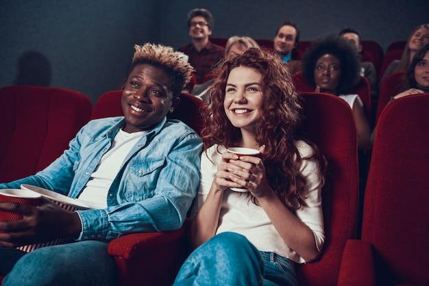 多民族のカップルが映画館で映画を見ています