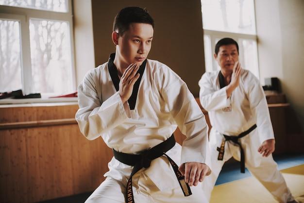 白い服と黒いベルトの人々はジムで訓練します。