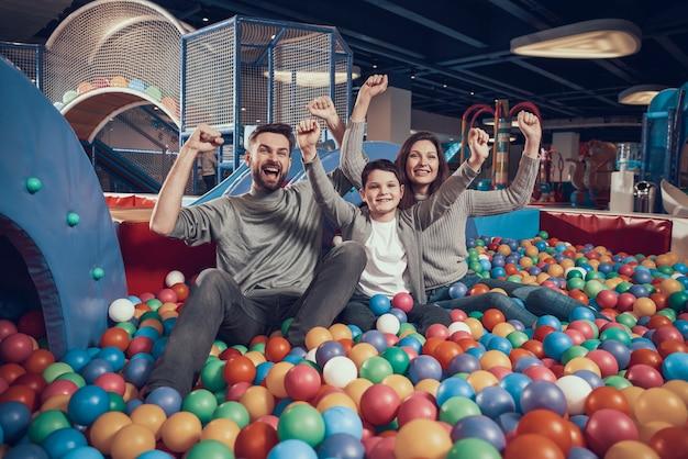 ボールとプールに座って喜んで家族