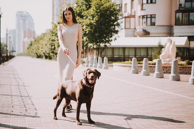 女性は街の遊歩道で彼女の犬と一緒に歩いています。