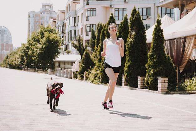 スポーツウーマンは都市遊歩道で犬と一緒に走っています。