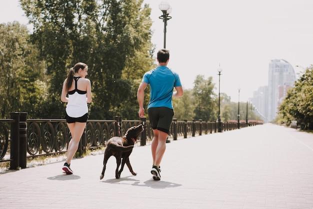 カップルが彼女の犬と一緒に街の道を走っています。