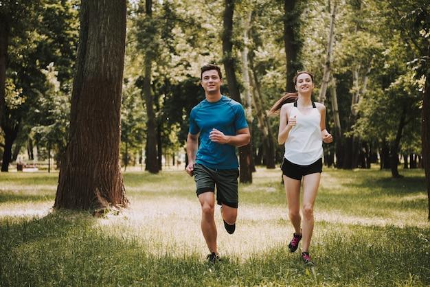 運動選手のカップルは緑豊かな公園で走っています。