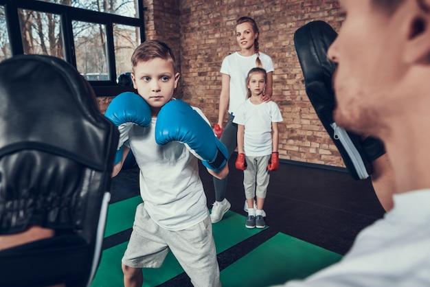 スポーツ家族はフィットネスクラブでボクシングトレーニングをしています