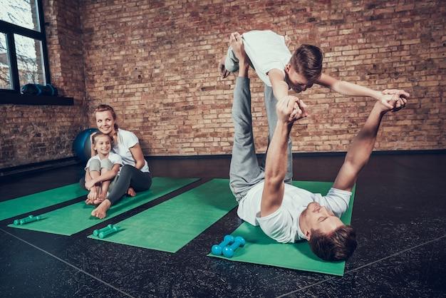 スポーツ家族のお父さんは足に息子のバランスをとっています。