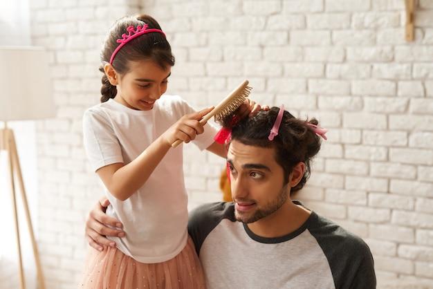 アラブ家族。女の子は新しいお父さんの髪型を作っています。
