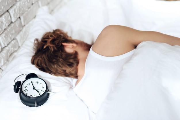 赤い髪の若い男が寝室で眠る