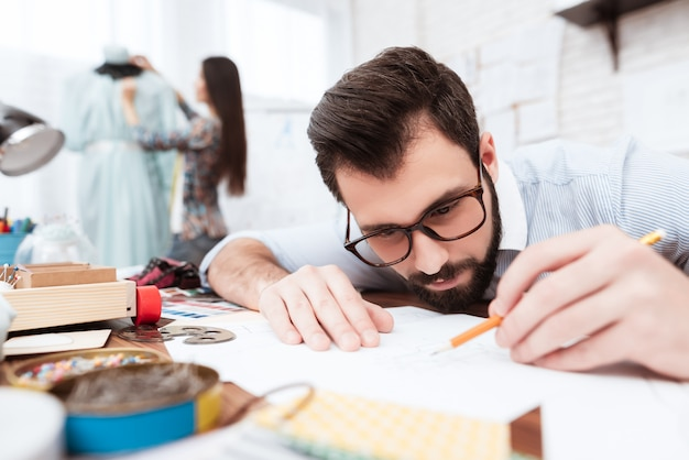 人のファッション・デザイナーが紙に描く