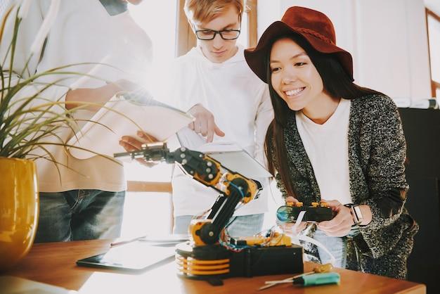 若い女性は機械式ロボットをテストしています