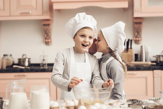 幸せな男の子と女の子が一緒に自宅のキッチンで調理する