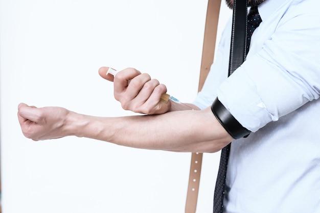 男は彼の手に注射をする
