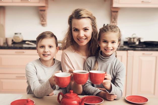 ママと子供たちはお茶素朴なビンテージ赤カップを持っています