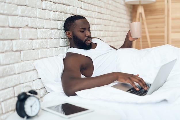 黒の目を覚ます男はベッドの中でコーヒーを飲む