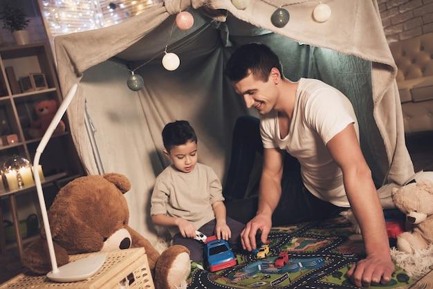 Отец и сын играют с автомобилями на ковровой дороге