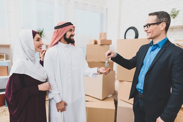 全米リアルター協会加入者は家の鍵に幸せなアラブ家族の動きを与えます
