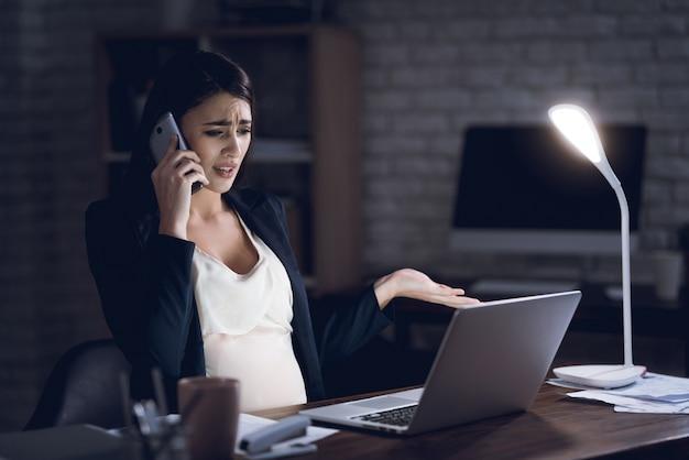 妊娠中の女性実業家のオフィスで働くことを強調