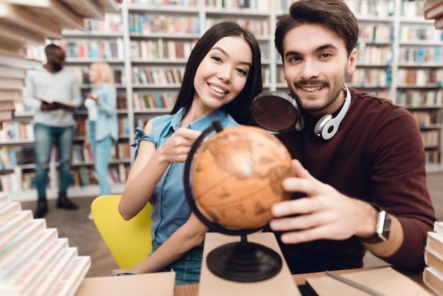 Умные студенты используют глобус в библиотеке