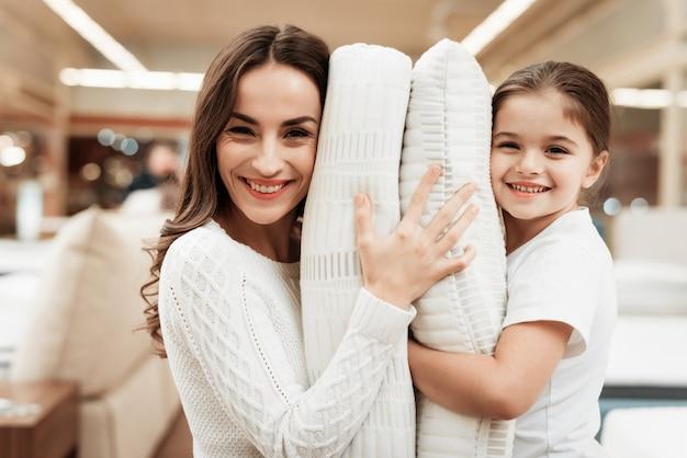 Счастливая маленькая девочка и молодая женщина обнимают подушки