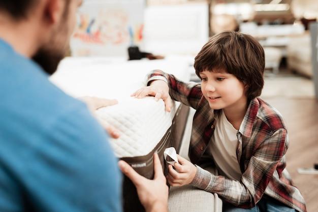 小さな男の子とハンサムな男のマットレスを選ぶ