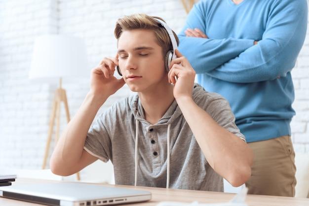 Сын слушает музыку в наушниках