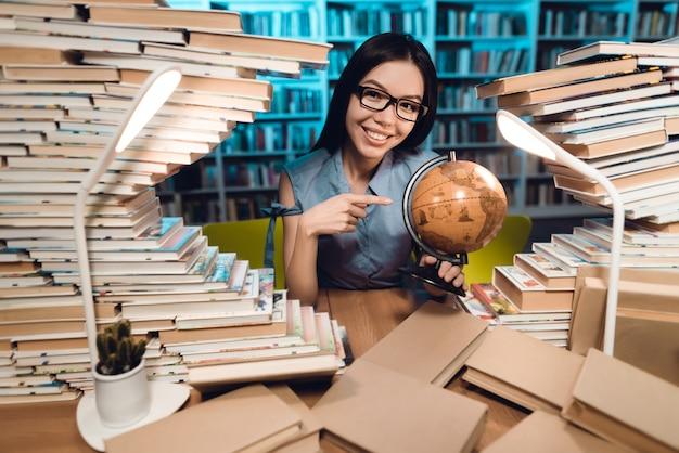 民族のアジアの女の子は図書館で地球を使用しています