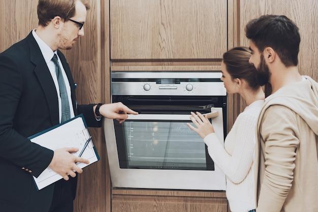 スーツを着たマネージャーがカップルのクライアントにビルトインオーブンを見せています