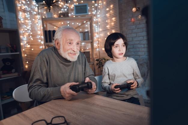 Внук играет в видеоигры с дедушкой