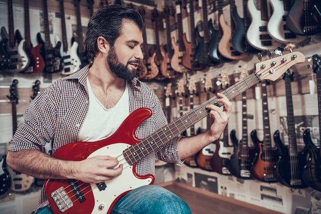 ひげを生やした男が音楽店で新しいギターをチェック