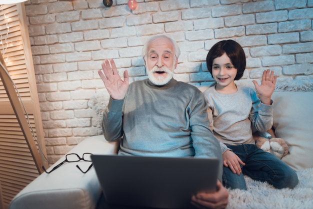 Улыбающийся дедушка с ребенком видео в чате на ноутбуке