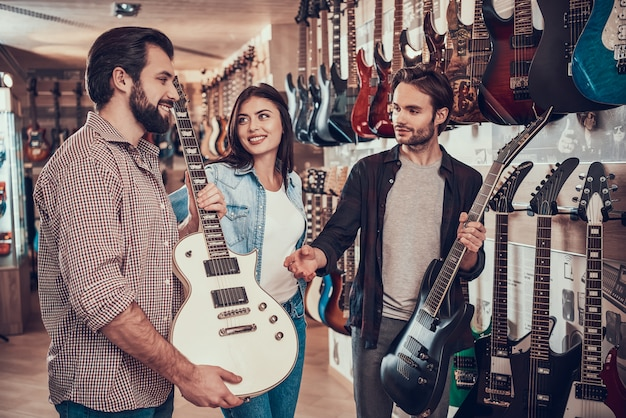 若いカップルがミュージックストアで新しいエレキギターを買う