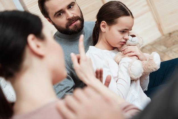 クローズアップの父は屋内でかわいい泣いている娘を抱擁します。