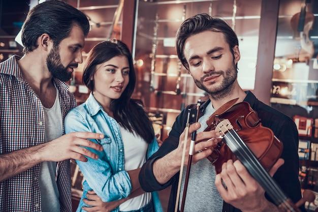 弓を持つ若い男はバイオリンを正しく保持する方法を示します