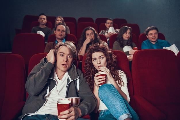 映画館でスリラーを見ておびえた若いカップル。