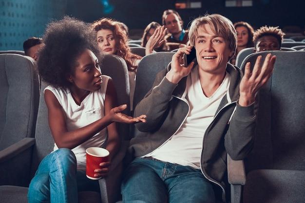 若い男は映画館で電話で通信します。