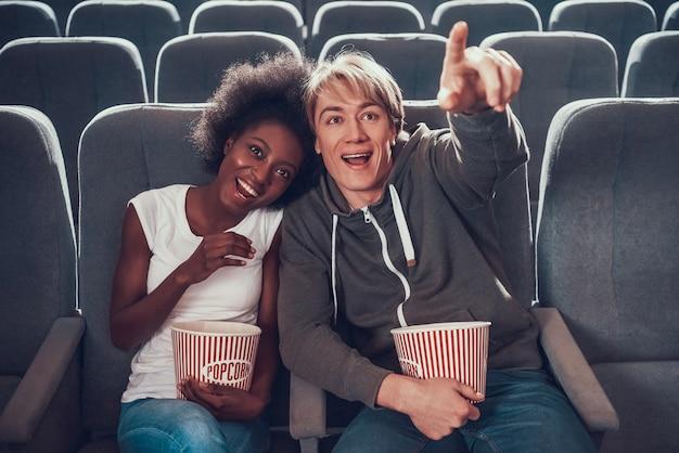 多国籍カップルは映画館でコメディーを見ています。
