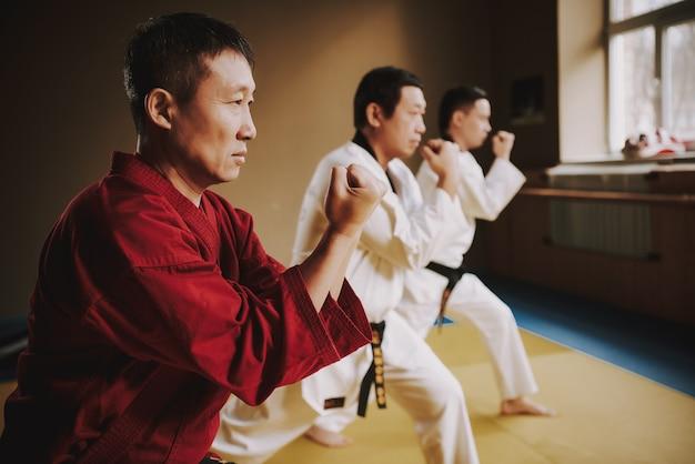 Сенсей и два студента боевых искусств в белых тренировках.